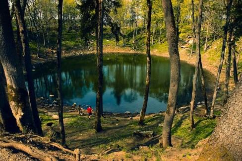 Resim 4. Kaali krateri. Estonya'nın Saarema adasında bir grup kraterin adıdır. 4000 yıl önce 20-80 ton ağırlığında bir meteor 10-20 km/s hızla düşerken 5-10 km yükseklikte parçalanıyor ve bu parçaların her biri yerde bir krater açıyor. En büyük parçanın açtığı kraterin çapı 110 m ve derinliği 22 m. Bu kraterin tabanında bugün Kaali gölü bulunmakta. Bu bombardıman sırasında meydana gelen çapları 12-40 m olan sekiz krater, büyük olan ile beraber bir kilometre kare içinde yer alıyor.